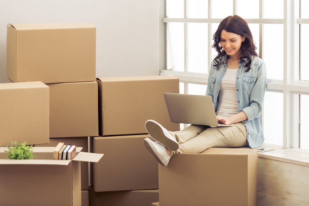 College Student Sitting on Moving Boxes