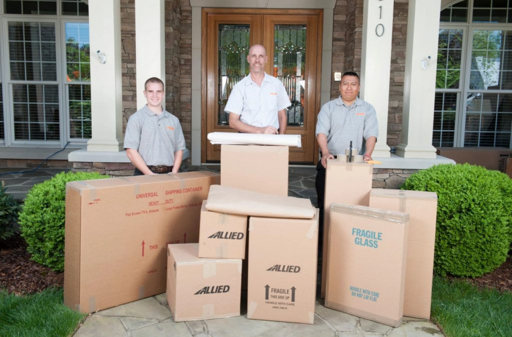 Three Allied Movers Behind Boxes in Front of a Home Porch